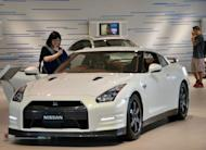Customers check a Nissan vehicle at the company's showroom in Yokohama, suburban Tokyo on Thursday. Nissan has posted a 15% drop in quarterly profit as a strong yen and weak European market dent earnings, but Japan's second-biggest automaker says its full-year forecast is on track