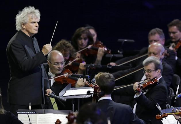FILE - This is a Friday, July 27, 2012, file photo of Sir Simon Rattle as he conducts an orchestra during the Opening Ceremony at the 2012 Summer Olympics in London. Conductor Simon Rattle is to swap
