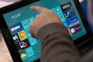 A man navigates with Windows 8 on a Tablet on November 14, 2012 in Paris. The tweaked version of Microsoft's operating system nicknamed Windows Blue will be previewed on June 26 and will be a free update for users as Windows 8.1, the company said Tuesday