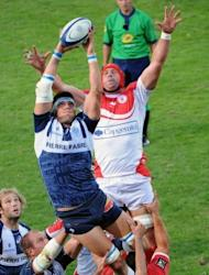 Castres' lock Christophe Samson (L) grabs the ball in a line-out despite Biarritz's lock Jerome Thion during the French Top 14 rugby union match at the Stadium Pierre Antoine in Castres, southern France. Castres won 28-13