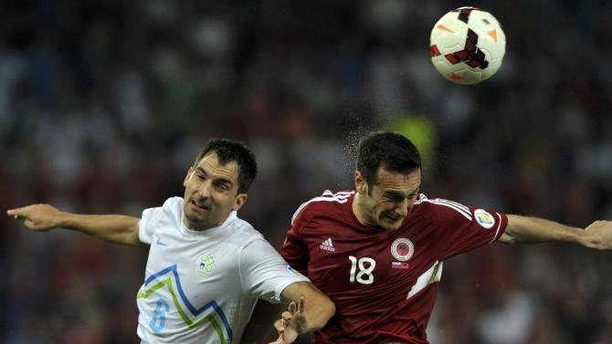 Ilic of Slovenia jumps for the ball with Salihi of Albania during their 2014 World Cup qualifying soccer match in Ljubliana
