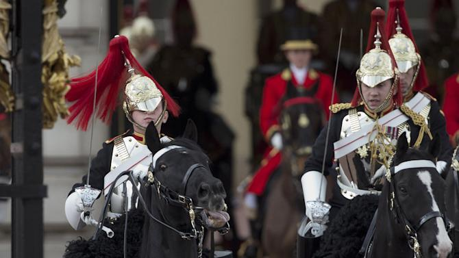 The helmet of a member of the Household Cavalry regiment, left, obscures his face as he struggles to keep control of his horse before Britain's Queen Elizabeth II left Buckingham Palace in her Irish State Coach, to deliver her speech at the State Opening of Parliament in London, Wednesday, May 8, 2013.  The British government says it will announce legislation to tighten immigration rules, reform pensions and reduce red tape for business when it lays out its legislative plans for the next year.  The measures will be announced by Queen Elizabeth II during the pageant of power, pomp and politics known as the State Opening of Parliament.  (AP Photo/Matt Dunham)