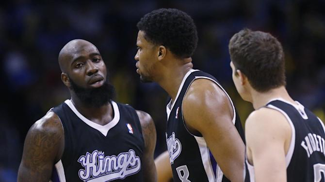 Sacramento Kings forward Rudy Gay (8) is surrounded by teammates forward Quincy Acy (5) and guard Jimmer Fredette (7) after being ejected from the game in the fourth quarter of an NBA basketball game against the Oklahoma City Thunder in Oklahoma City, Sunday, Jan. 19, 2014. Oklahoma City won 108-93