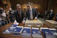 Copies of President Barack Obama's proposed fiscal 2015 budget are set out for distribution by Senate Budget Committee Clerk Adam Kamp, center, on Capitol Hill in Washington, Tuesday, March 4, 2014. President Barack Obama is unwrapping a nearly $4 trillion budget that gives Democrats an election-year playbook for fortifying the economy and bolstering Americans' incomes. It also underscores how pressure has faded to launch bold, new attacks on federal deficits. (AP Photo/J. Scott Applewhite)
