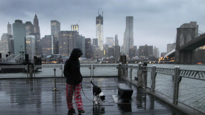 Vanessa Pumo walks her dog Bella as wind and rain from Hurricane Sandy arrive, Monday, Oct. 29, 2012 in Brooklyn, N.Y. Behind her is the Manhattan skyline and Brooklyn Bridge, right. (AP Photo/Mark Lennihan)