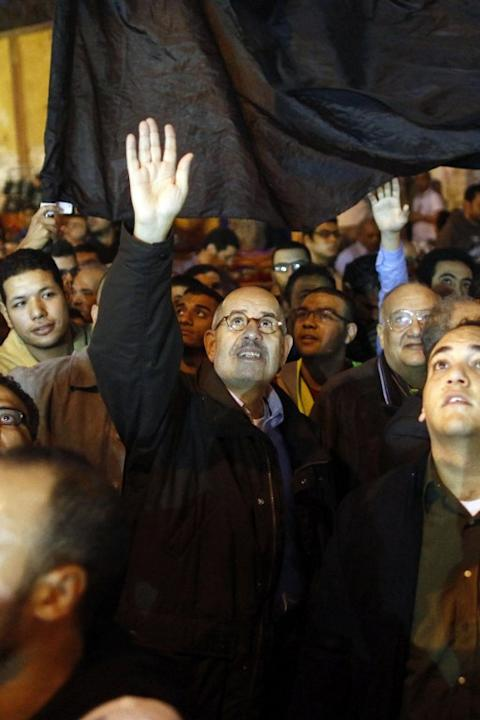 Egyptian opposition leader and Nobel Prize Laureate Mohammed el Baradei waves as he leads a march to join the tens of thousands people taking part in a mass rally against a decree by President Mohamed