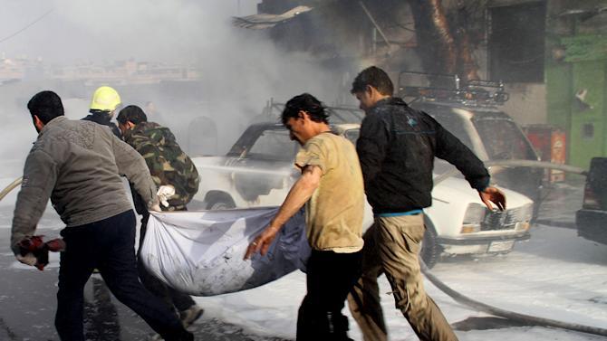 In this photo released by the Syrian official news agency SANA, Syrian citizens carry a dead body, at the scene where two mortar rounds exploded near an orphanage, at al-Boukhtyar area, in Damascus, Syria, Wednesday March 13, 2013. The state-run SANA news agency said two mortar rounds exploded near an orphanage in al-Boukhtyar area, killing and wounding an unknown number of people. Syrian government troops fought fierce battles with rebels on Wednesday for control of key neighborhoods in the north of Damascus, residents and activists said. (AP Photo/SANA)