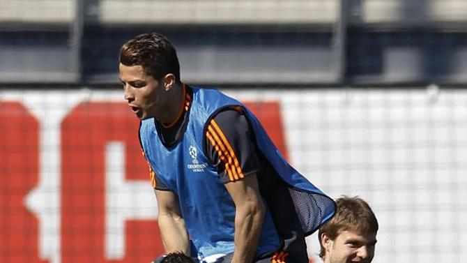 Real's Cristiano Ronaldo, left, jumps on top of Angel Di Maria from Argentina, bottom, during a training session prior to the Champions League second leg knock out soccer match between FC Schalke 04 and Real Madrid in Madrid, Spain, Monday, March. 17, 2014. (AP Photo)