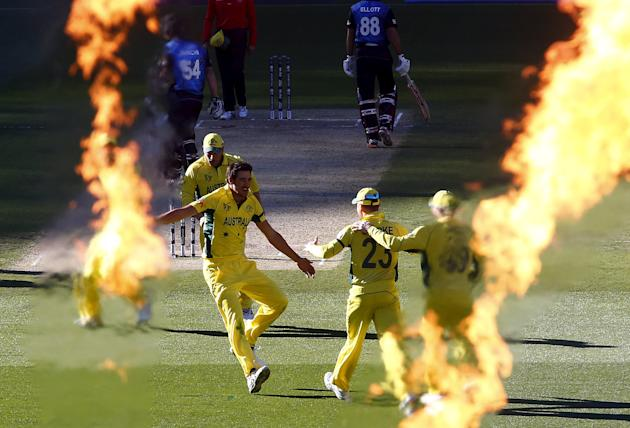 Australia's Mitchell Starc celebrates with captain Michael Clarke after they dismissed New Zealand's Luke Ronchi for a duck during their Cricket World Cup final match at the MCG