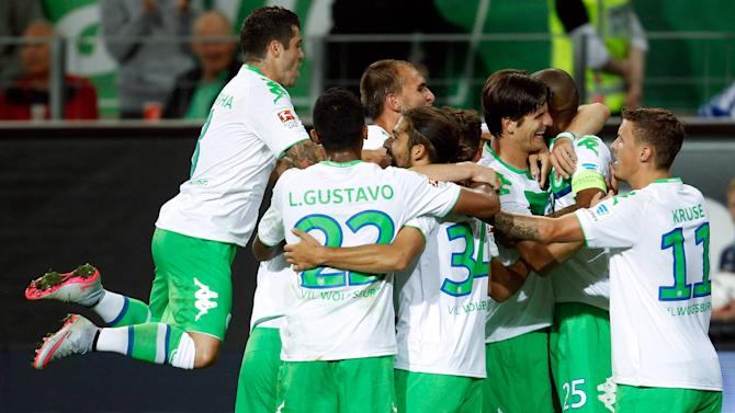 Wolfsburg players celebrate a goal against Schalke 04 during their Bundesliga first division soccer match in Wolfsburg
