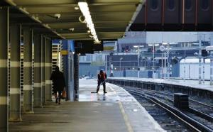 A man sweeps an empty platform at Waterloo Station after numerous trains were cancelled due to storms in London