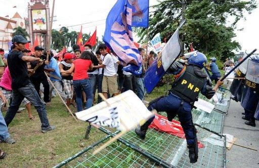 Anti-government protesters clash with police during a demonstration in Manila