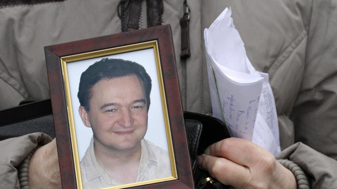 In this Monday, Nov. 30, 2009 file photo a portrait of lawyer Sergei Magnitsky who died in jail, is held  by his mother Nataliya Magnitskaya, as she speaks during an  interview with the AP in Moscow. U.S. lawmakers are expected to vote in a human rights legislation named after Magnitsky that would impose sanctions on Russian officials involved in human rights violations. (AP Photo/Alexander Zemlianichenko, File)