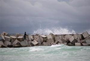 A man fishes while standing on wave breakers in Cancun