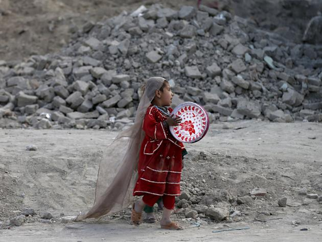 Afghan girl plays a tambourine outside her house in Kabul, Afghanistan