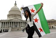 An anti-Assad protester carries the Syrian freedom flag in front of the U.S. Capitol in Washington September 9, 2013. REUTERS/Kevin Lamarque