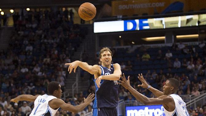 Dallas Mavericks's Dirk Nowitzki, center, passes the ball as Orlando Magic's Doron Lamb (1) and Maurice Harkless defend during the second half of an NBA basketball game in Orlando, Fla., Saturday, Nov. 16, 2013