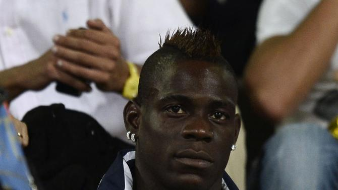 Italy's Balotelli sits in the tribune during the World Cup qualifying soccer match against Bulgaria in Palermo
