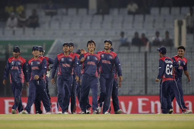 Nepal cricketers congratulate bowler Shakti Gauchan, front, after taking a wicket during their ICC Twenty20 Cricket World Cup match against Hong Kong in Chittagong, Bangladesh, Sunday, March 16, 2014.