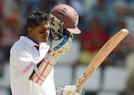 West Indies batsman Shivarine Chanderpaul celebrates his 10,000th test run during the fourth day of the third test match between the West Indies and Australia in Roseau, Dominica