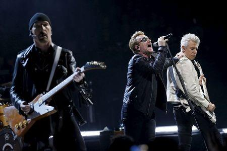 Foto del domingo de Bono (C), the Edge (I) y Adam Clayton (D), integrantes de U2, tocando en París
