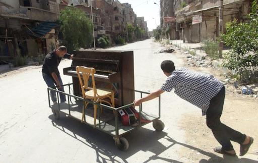 File picture shows Aeham al-Ahmad, a former resident of Damascus' Yarmuk Palestinian refugee camp, being helped by a friend to push his piano along a the street in the southern Damascus suburb