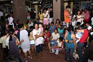 Residents gather at the provincial capital building in Tandag City, Surigao Del Sur Province, in the southern island of Mindanao on August 31, 2012. Families returned to their quake-devastated homes in the central Philippines Sunday, ignoring government warnings to relocate away from danger zones