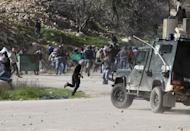 Palestinian protesters throw stones towards an Israeli police vehicle during clashes in front of Ofer prison, near the West Bank city of Ramallah, on February 15, 2013. Thousands rallied in the West Bank's two largest cities on Monday in support of four long-term hunger strikers, as the Palestinians demanded tougher EU action to help their prisoners