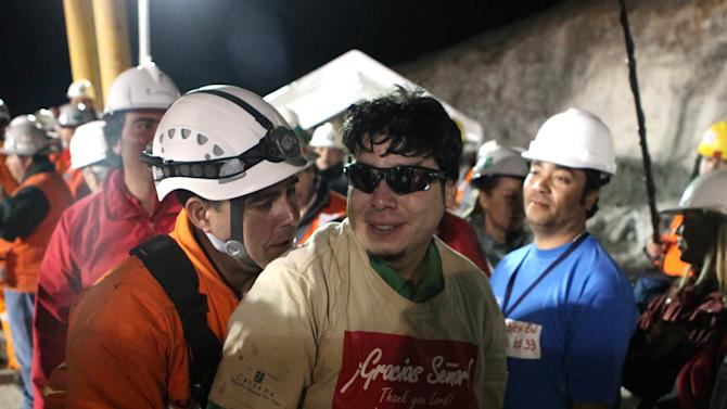FILE - In this Oct. 13, 2010 file photo released by the Chilean government, miner Pedro Cortez, center, is helped by rescue workers after being pulled out of the San Jose gold and copper mine near Copiapo, Chile. One of the myths surrounding the 33 miners who survived 69 days, 700 feet deep, and whose unprecedented and dramatic rescue was beamed to millions around the world, is that they are millionaires and do not need work. A year after the tragedy, nearly half are unemployed, one lives the fame that began to take shape at the bottom of the mine, many have chosen to give motivational talks to make a living and and four returned to work in the mines.  (AP Photo/Chilean Government, Hugo Infante)