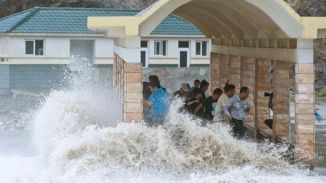 People dodge as a storm surge hits the coastline under the influence of Typhoon Fitow in Wenling, Zhejiang province