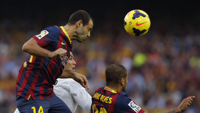 Barcelona's Javier Mascherano from Argentina, left, and Daniel Alves from Brazil, right, jumps for the ball with Real Madrid's Cristiano Ronaldo from Portugal during a Spanish La Liga soccer match between Barcelona F.C. and Real Madrid at the Camp Nou stadium in Barcelona, Spain,  Saturday, Oct. 26, 2013