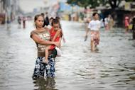 Picture taken on August 10, shows a woman holding a young boy as she wades through floodwaters in a street in the township of Apalit on the outskirts of Manila. Deadly floods, power blackouts and traffic gridlock, many of Asia's biggest cities are buckling under the strain of rapid economic development, extreme weather and an exodus from the countryside