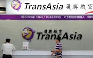 Journalists wait in front of a TransAsia reservations desk at Sungshan airport in Taipei, on July 23, 2014