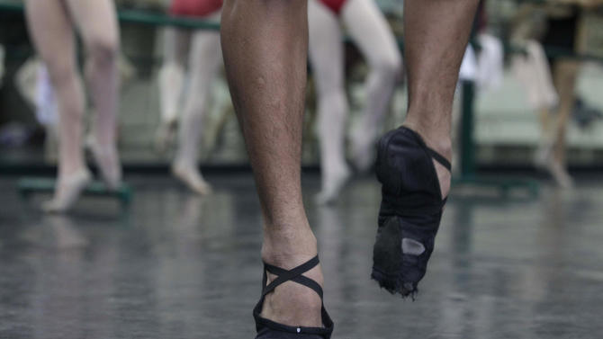 In this photo taken Nov. 25, 2012, Filipino slum dweller Jamil Montebon uses his worn-out ballet shoes as he practices steps during a class at Ballet Manila in the Philippine capital. Montebon, a scholar at Ballet Manila's program, used to collect garbage and also worked at a junk shop. He now receives a monthly stipend, stays at their dormitory and is given meals. (AP Photo/Aaron Favila)