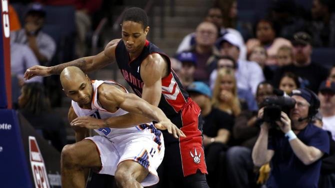 Charlotte Bobcats guard Gerald Henderson, left, and Toronto Raptors guard DeMar DeRozan fight for a loose ball in the first half of an NBA basketball game Monday, Jan. 20, 2014 in Charlotte, N.C