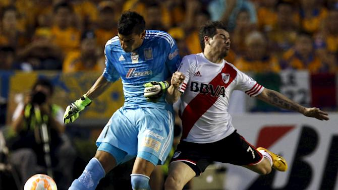 Goalkeeper Nahuel Guzman of Mexico 's Tigres fights for the ball with Rodrigo Mora of Argentina's River Plate during the first leg of their Copa Libertadores final soccer match at the Universitario stadium in Monterrey