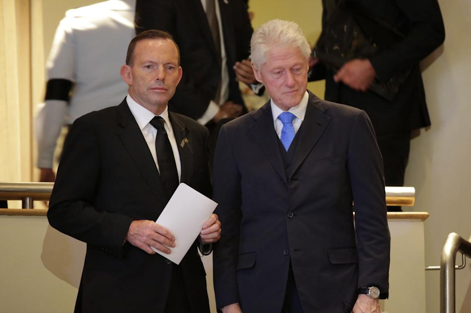 Australia's Prime Minister Tony Abbott, left, and former U.S. President Bill Clinton, right, attend a state funeral for the late Lee Kuan Yew, at the University Cultural Center, Sunday, March 29,