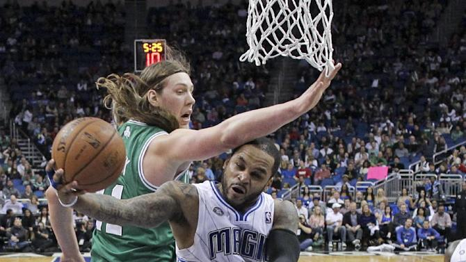 Orlando Magic's Jameer Nelson, center, gets around Boston Celtics' Kelly Olynyk, left, for a shot in the first half of an NBA basketball game in Orlando, Fla., Sunday, Jan. 19, 2014. Orlando won 93-91