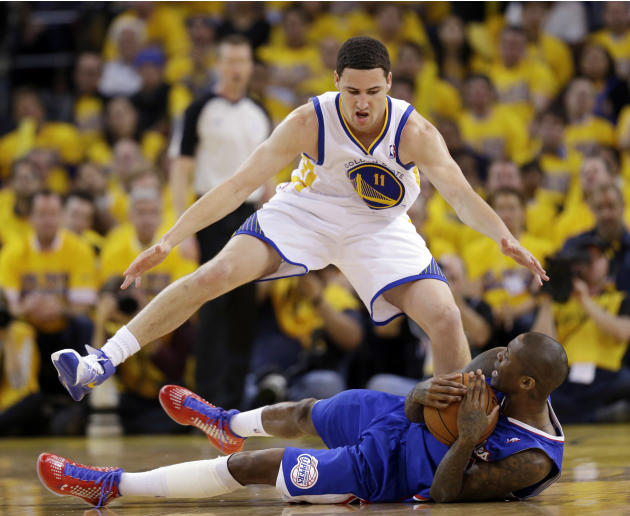 Los Angeles Clippers' Jamal Crawford, bottom, hangs on to the ball as Golden State Warriors' Klay Thompson (11) defends during the second half in Game 3 of an opening-round NBA basketball play