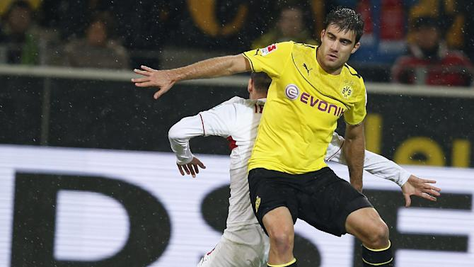 Stuttgart's Vedad Ibisevic of Bosnia, rear, and Dortmund's Sokratis of Greece challenge for the ball during the German first division Bundesliga soccer match between  BvB Borussia Dortmund and VfB Stuttgart  in Dortmund, Germany, Friday, Nov. 1, 2013