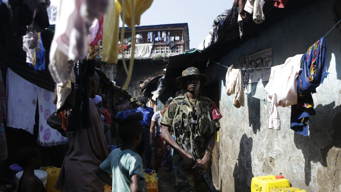 Security forces walk through the Mabella slum after breaking up a domestic dispute and arresting several residents, in Freetown, Sierra Leone Friday, Nov. 16, 2012. Ten years after the end of a devastating civil war, Sierra Leone will go to the polls on Saturday to choose between candidates including incumbent President Ernest Bai Koroma and opposition leader Julius Maada Bio. With maintaining a peaceful atmosphere around the vote a top priority, the police force, reinforced by other security forces, is taking a proactive approach. (AP Photo/Rebecca Blackwell)