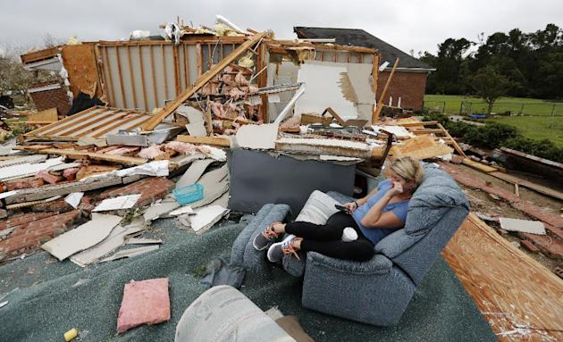 Hilary Benjamin sits in a recliner that belongs to her good friends Julie and John Bercik, after what is believed to be a tornado hit their house on Sonny Boy Lane in Johns Island, S.C., Friday, Sept.