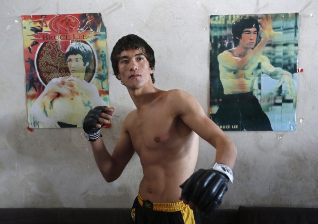 Abbas Alizada poses for a picture in front of Bruce Lee posters in Kabul. (Reuters)