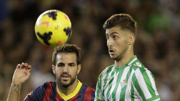 Barcelona's Francesc Fabregas, left, and Betis' Alvaro Vadillo, right, eye the ball during their La Liga soccer match at the Benito Villamarin stadium, in Seville, Spain, Sunday, Nov. 10, 2013