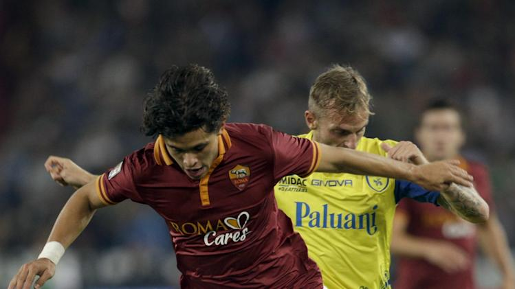 AS Roma defender Dodo' of Brazil, foreground, is challenged by Chievo midfielder Luca Rigoni during a Serie A soccer match between AS Roma and Chievo, at Rome's Olympic stadium, Thursday, Oct. 31, 2013