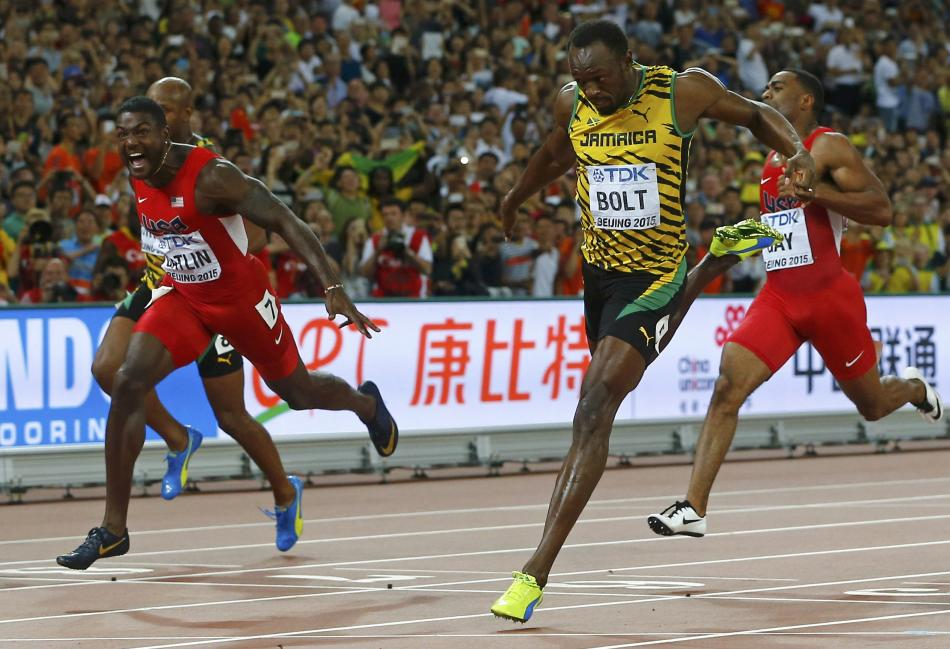 Gatlin of the U.S. and Bolt of Jamaica cross the finsih line in the men's 100 metres final during the 15th IAAF World Championships at the National Stadium in Beijing
