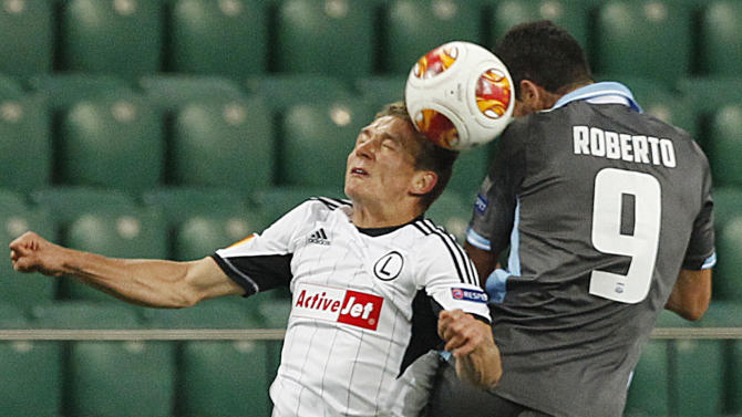 Roberto,right, of Apollon Limassol FC challenges for the ball with Jakub Rzezniczak,left, of Legia Warsaw, during their Europa League group J soccer match at in Warsaw, Poland, Thursday, Oct. 3, 2013