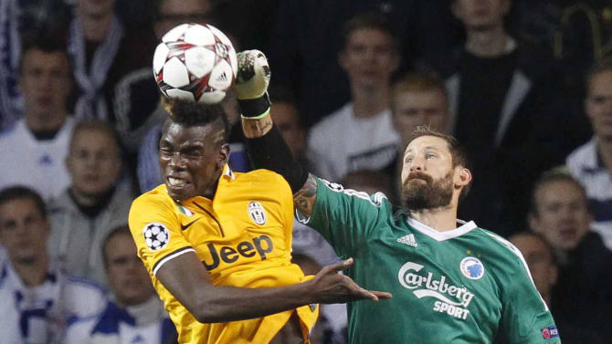 Paul Pogba of Juventus , left, and FC Copenhagen's goalkeeper Johan Viland of Sweden compete for the ball during their Champions League Group B soccer match at the Parken Stadium, Copenhagen, Denmark, Tuesday Sept. 17, 2013