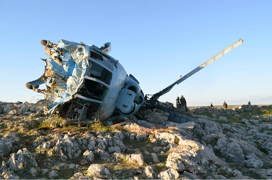 Nusra Front fighters inspect a helicopter that belongs to forces loyal to Syria's President Bashar Al-Assad after it crashed in Jabal al-Zawiya in the southern countryside of Idlib