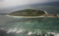 Photographed through the window of a closed aircraft, an aerial view shows Pagasa Island, part of the disputed Spratly group of islands, in the South China Sea located off the coast of western Philippines Wednesday July 20, 2011. China protested a trip made by Filipino lawmakers to disputed areas in the South China Sea to assert the claim of the Philippines. Ethan Sun, spokesman for the Chinese embassy in Manila, said the trip scheduled was 'against the spirit' of a code of conduct signed by claimants to the areas in 2002. The Spratlys, believed to be rich in oil, mineral and marine resources, are also claimed in whole or partly by Brunei, Malaysia, Vietnam and Taiwan. (AP Photo/Roley Dela Pena, Pool)